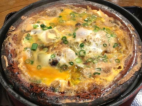 平たい土鍋で具材を甘辛く煮込み、最後に卵でとじる